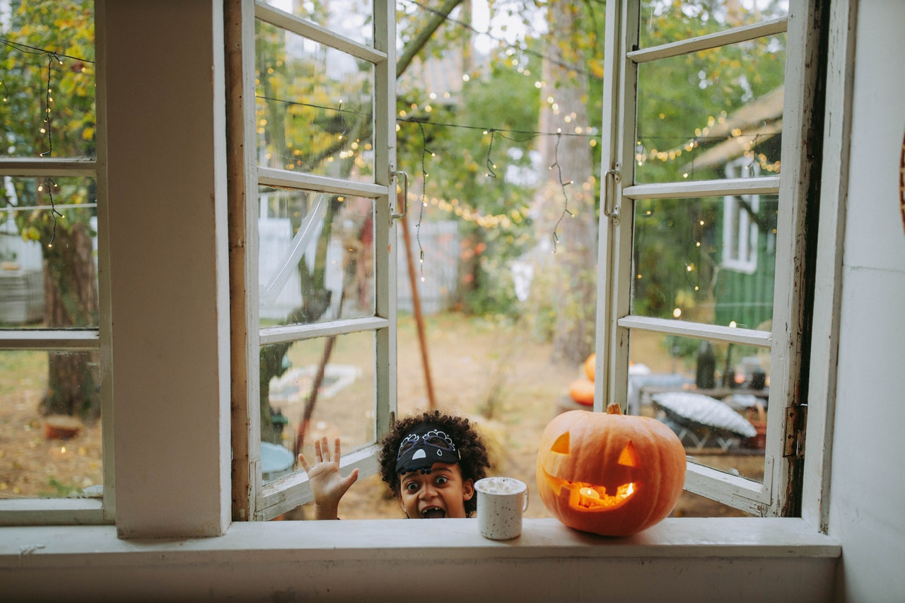 Young boy looking into window next to pumpkin and Halloween decorations.