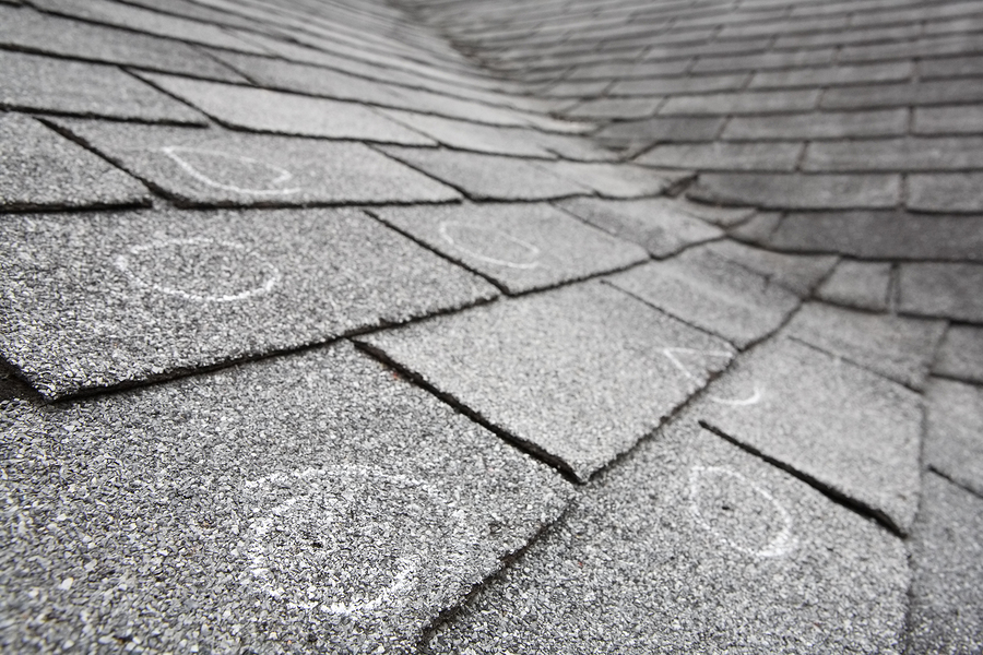 Old roof with hail damage, chalk circles mark the damage. Shallow depth of field